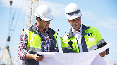 Two oilfield engineers poring over oilwell construction plans